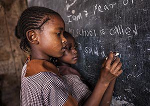 Young girls at an orphanage in Kenya learn is a classroom with no electricity