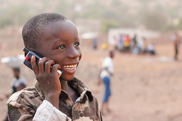 Image of smiling child in Africa talking on a mobile phone