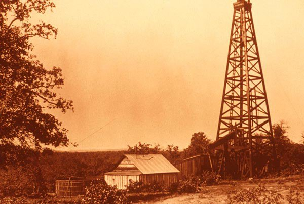 Image of a derrick and well site from the 1920s